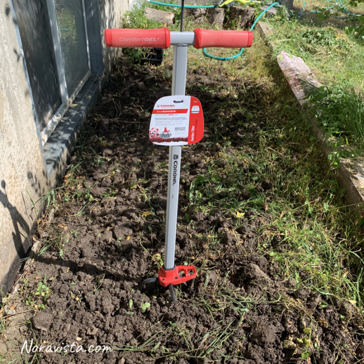 A garden tilling tool standing in a small garden box