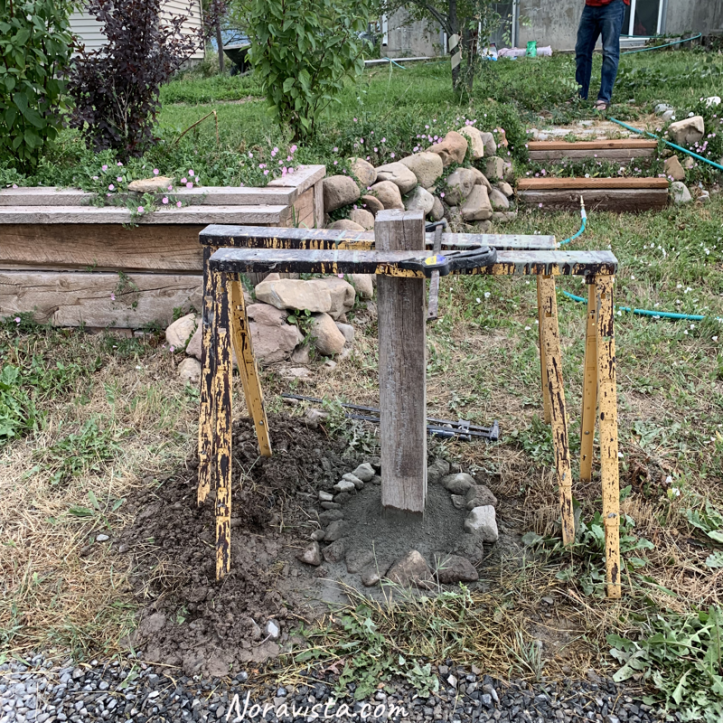 An oak 4x4 cemented in the ground with sawhorses and clamps around it for support