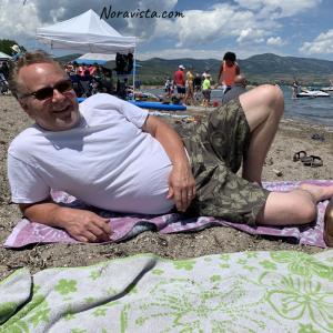 A man laying on the beach at Bear Lake Utah