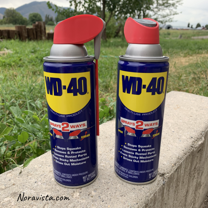 WD-40 spray cans sitting on a cement wall in a yard in Northern Utah