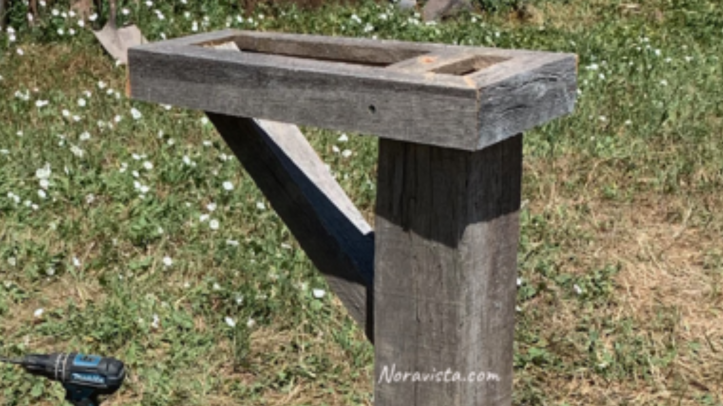 An oak mailbox post with a frame and support for the mailbox to be placed upon