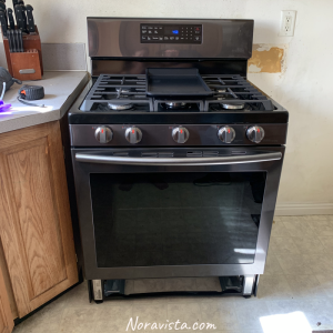 A new black stainless steel oven installed in a kitchen.