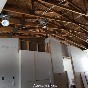A ceiling with bare trusses and new construction can lights with wires installed