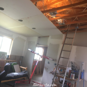 A room under construction with a drywall jack and ladder in the room with the drywall partially finished