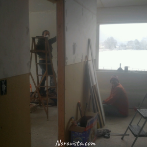A man and woman with masks on while sanding drywall