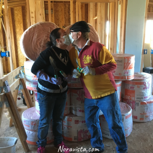 A man and woman standing in front of a bunch of rolls of insulation in a bare construction room kissing