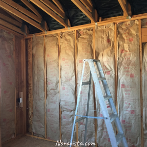 A wall with rolls of insulation installed, and attic soffits on the roof corners