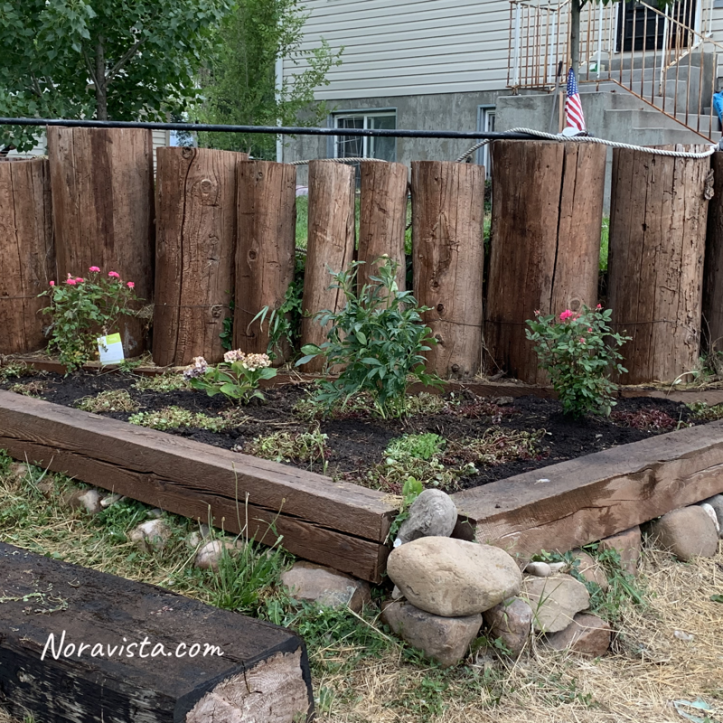 Logs stood up on their ends and a triangle flower box in front of them housing roses, peonies and Hydrangeas