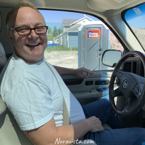A man in a truck with a potapotty outside in the background